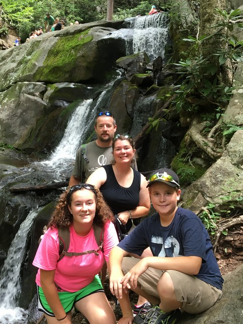 Jenifer and her family in front of a waterfall