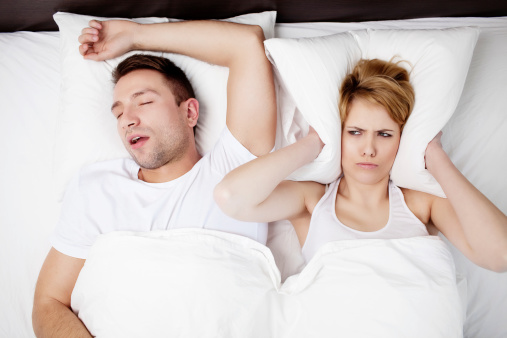 Couple in bed with the man snoring and woman holding a pillow over her ears