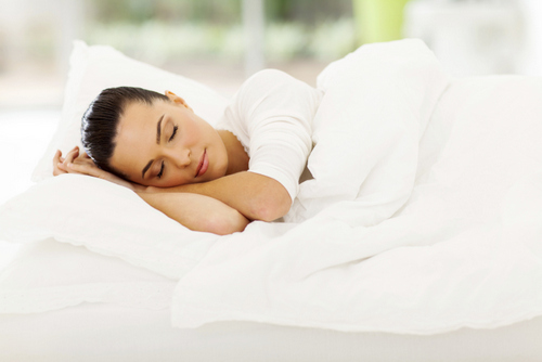Woman peacefully sleeping in a white bed